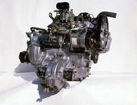 シリンダーヘッド、同ブロック、クランクケースからトランスミッションケース、クラッチハウジングまでアルミ合金によるダイキャスト製で、「白いエンジン」と呼ばれたDA型エンジン。写真は搭載位置に対して前方から見たところで、ファイナルドライブ(デファレンシャル)が手前にあることからおわかりのように、エンジンは後車軸より後方に横向きにオーバーハングされる。