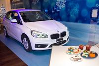 「BMW 218iアクティブツアラー」とカフェのフードメニュー。