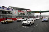 トヨタが所蔵するオープン仕様の「2000GTボンドカー」と、2000GTを実際に製作したヤマハの所蔵車である金色の2000GTを先頭に、オーナーズクラブのメンバーの2000GTおよび「スポーツ800」がホームストレート上に整列。