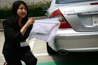 女性が手にしている白いハンカチは、メルセデス・ベンツ E320CDIの排気管をふさぐように被せておいたもの。白さが失われていないことがアピールされた。