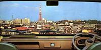 インパネおよび「パノラミック・ウィンドウ」と称したウインドシールドからの眺め。どこから撮影されたのだろうか、東京タワーがそびえ立つ昭和30年代の東京の風景である。