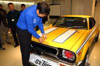 レストアの仕上げとして、ボンネットにエンブレムを装着する日産名車再生クラブの木賀新一代表。