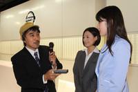 「ミス・フェアレディ」に突撃インタビューを敢行中のユニークな自動車評論家(?)「マリオ二等兵」。マリオ氏いわく「1995年に東京モーターショーを見るために初めて上京した際に、自動車メーカーのショールームをいくつか回ったが、こちらの対応にもっとも感動した」とのこと。