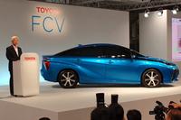 """今回の説明会では、FCV市販予定車のエクステリアのみ公開された。傍らに立つのは、「FCVで""""水素社会""""の一翼を担いたい」と語るトヨタ自動車の加藤光久 副社長。なお、FCVはあくまで燃料電池車の略称で、市販車のモデル名ではない。"""