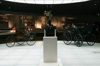 写真左がカール・ベンツの手になる最初のクルマ「パテント・モトールヴァーゲン」。右は馬車にエンジンを搭載した「ダイムラー・モトールクッツェ」。