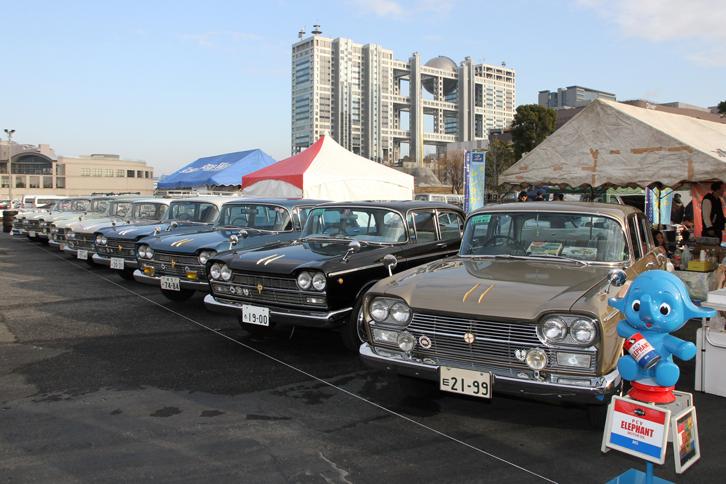 """初代「日産セドリック」の3つのクラブがジョイントして、クラブスタンドに1963年から65年までの通称""""横目のセドリック""""8台をズラリと並べていた。セダンの「デラックス」と「カスタム」、5ナンバーの「エステートワゴン」、4ナンバーの「バン」がそろっていたが、いずれも1.9リッター直4 OHVエンジンを搭載する。"""