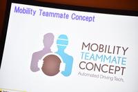 トヨタの自動運転の考え方を示す「Mobility Teammate Concept」のロゴマーク。システムが人に寄り添い、常時バックアップしている図案が添えられる。