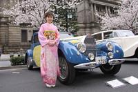 桜、名車とくれば、欠かせないのは美女? ということで、桜模様の和服姿のお嬢さんと1937年「ブガッティT57ヴァントー」のツーショット。品川や練馬といった陸運所在地の表記がなかった時代の東京ナンバーを付けた、古くから日本にある有名な個体である。
