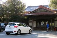 谷保天満宮の駐車場にて。奥に見える建物は参集殿。かつては結婚式などに使われていたとのことです。