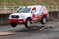 特設コースで豪快にジャンプする、パリダカ仕様の「ランドクルーザー」。三橋淳選手のドライブで、同乗体験が可能。