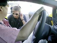 ドライバーズシートの後ろに付けられたウォーキートーキー(トランシーバー)をチェックしに来たインストラクター。先導車から走りながら、またはコース脇に立って指示を出す。ドライバーは、自動車専門誌『Car Graphic』の高平高輝記者。